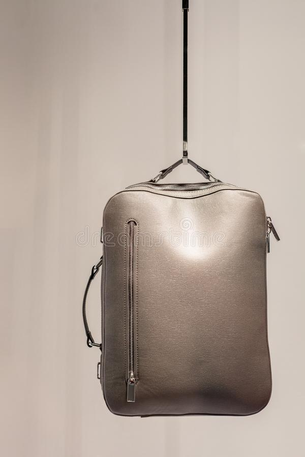 Womens silver color leather backpack in shop. Gray Satchel bag stock photography