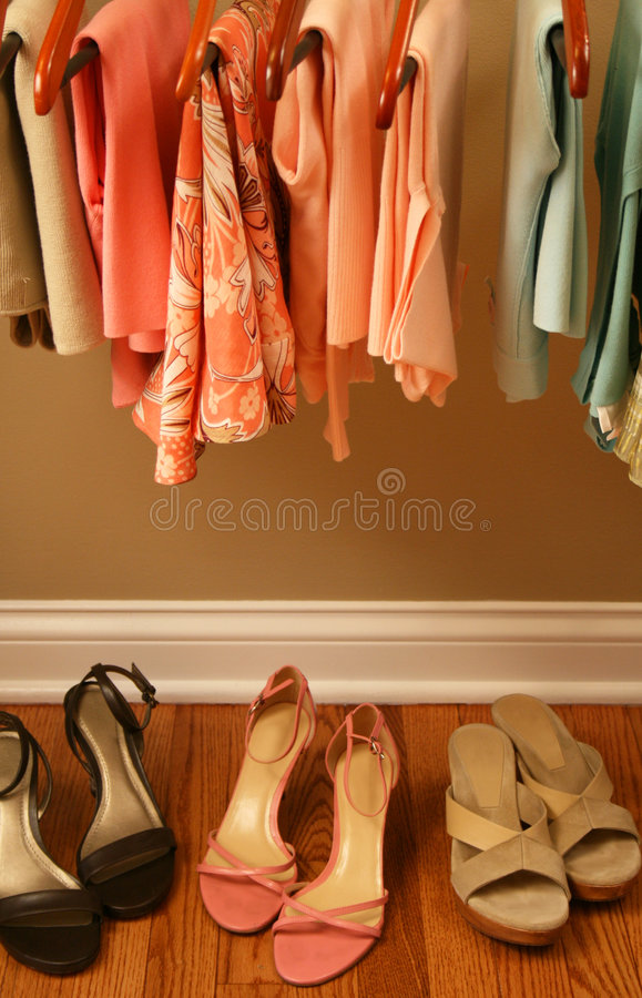 Womens spring clothing in closet. Ladies pastel spring clothing hanging on matching wooden hangers in closet stock photography