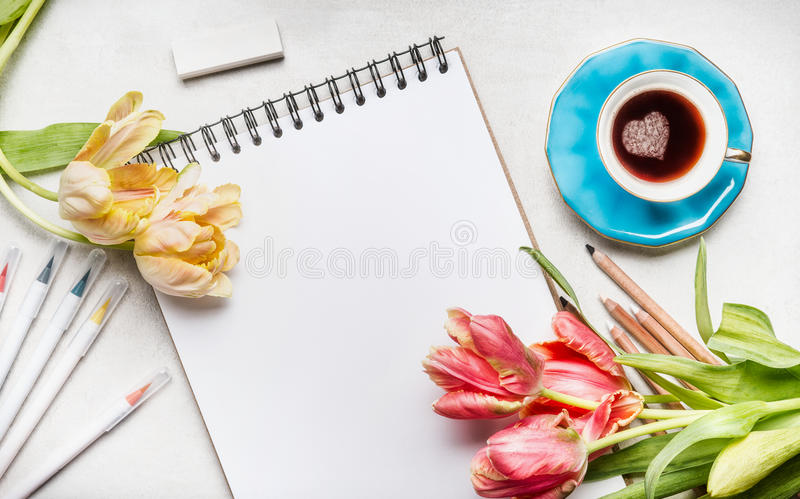 Womens springtime workspace with pretty tulips, notebook or sketchbook , colorful brush markers and coffee cup. Top view royalty free stock photos
