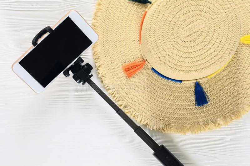 Womens summer accessories straw hat, cellphone, selfie stick o. N white wooden background with copy space. Fashion travel concept. Flat lay royalty free stock photography
