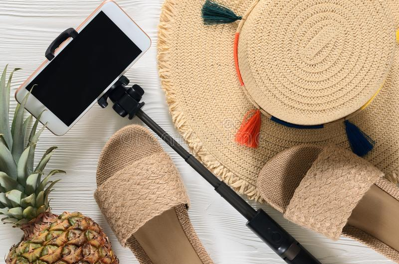 Womens summer accessories straw hat, cellphone, selfie stick,. Pineapple on white wooden background. Fashion look, travel and summer concept. Flat lay. Natural royalty free stock image