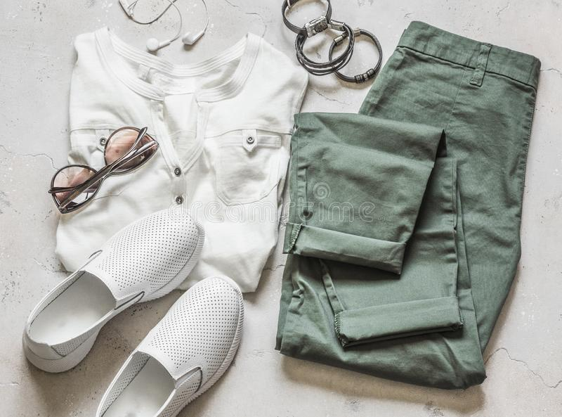 Womens summer clothes - olive cotton pants, white short sleeve t-shirt, white leather sports shoes, sunglasses, bracelets on a stock photography