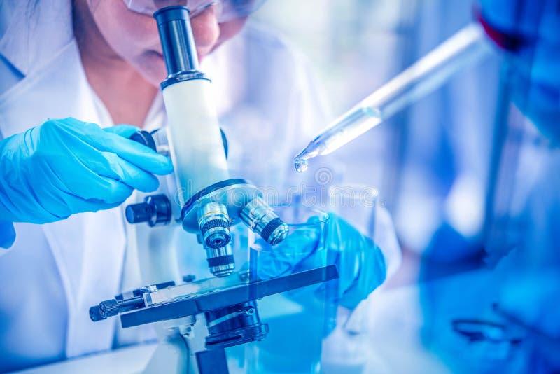 Womenscientist que olha através do microscópio no laboratório Cientista novo que faz alguma pesquisa com exposição dobro química  imagem de stock