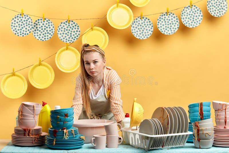 Womna biondo esaurito che si appoggia il tavolo da cucina e che esamina la macchina fotografica fotografia stock
