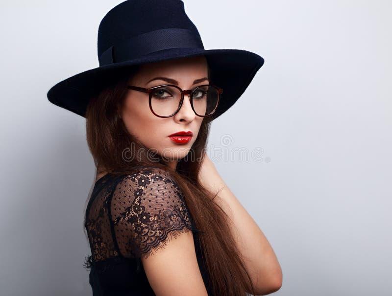 Womna sexy de maquillage de charme dans les verres et le chapeau bleu-foncé l de mode photo libre de droits