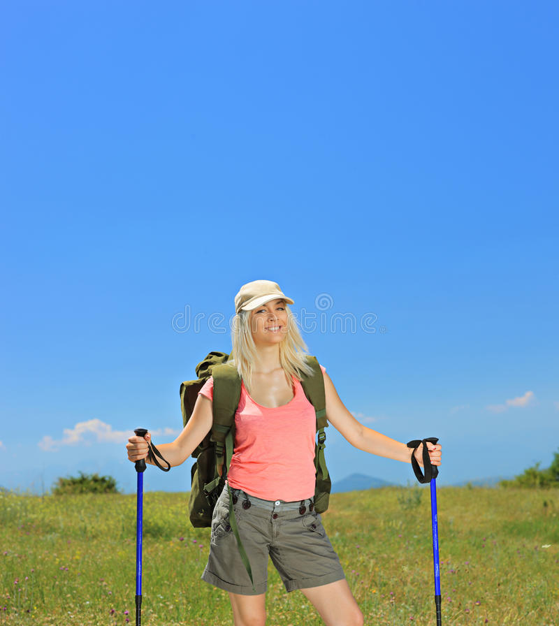 A womqh with backpack and hiking poles posing