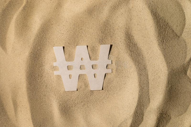 Won Sign On the Sand. South Korean Won Symbol lies on the Sand in Direct Sunlight royalty free stock photo