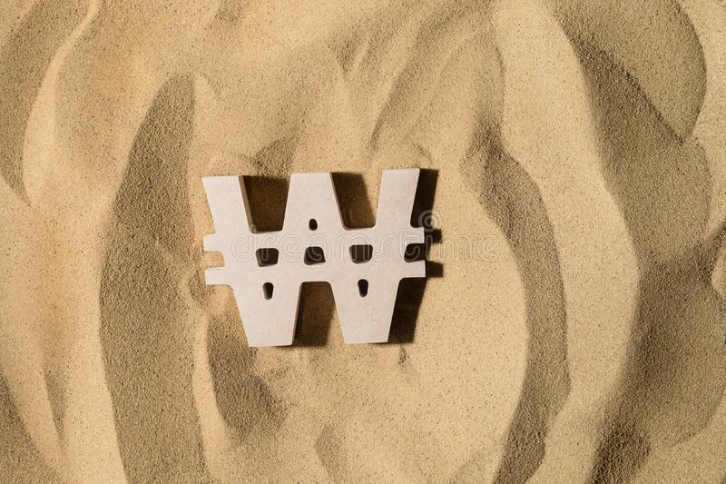 Won Sign On the Sand. South Korean Won Symbol lies on the Sand in Direct Sunlight stock photo