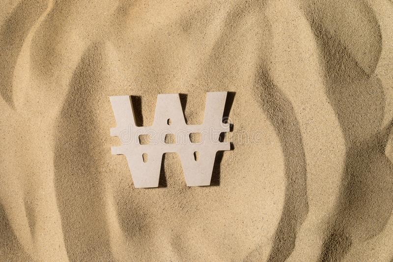 Won Sign On the Sand. South Korean Won Symbol lies on the Sand in Direct Sunlight royalty free stock photography
