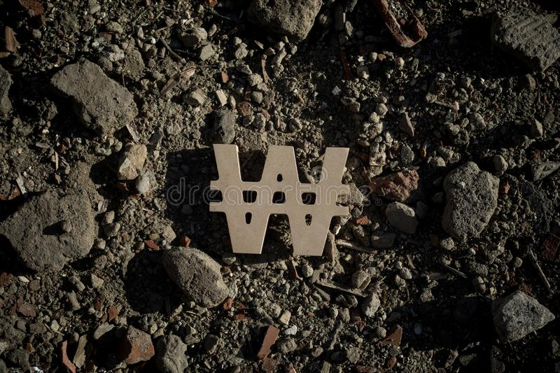 Korean Won Symbol on Construction Dirt. South Korean Won Sign on Dirt of Building Debris in Harsh and Dark Shadow with Depressive Atmosphere royalty free stock photos