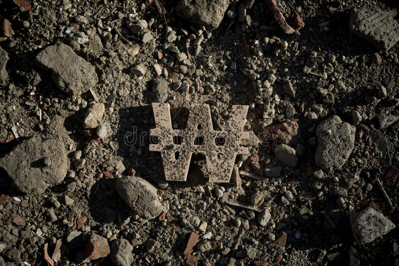 Won Symbol on Dirt or Debris. South Korean Won Sign on Dirt of Building Debris in Harsh and Dark Shadow with Depressive Atmosphere stock photos