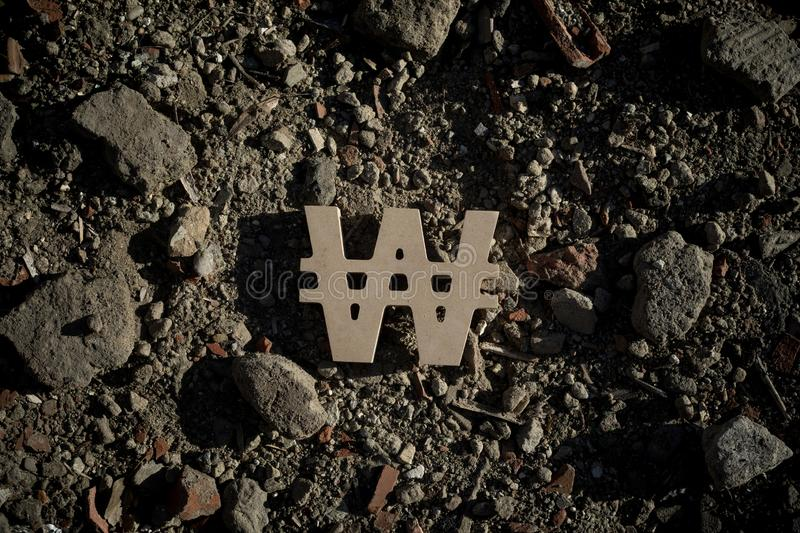 Won Symbol on Dirt. South Korean Won Sign on Dirt of Building Debris in Harsh and Dark Shadow with Depressive Atmosphere royalty free stock photos