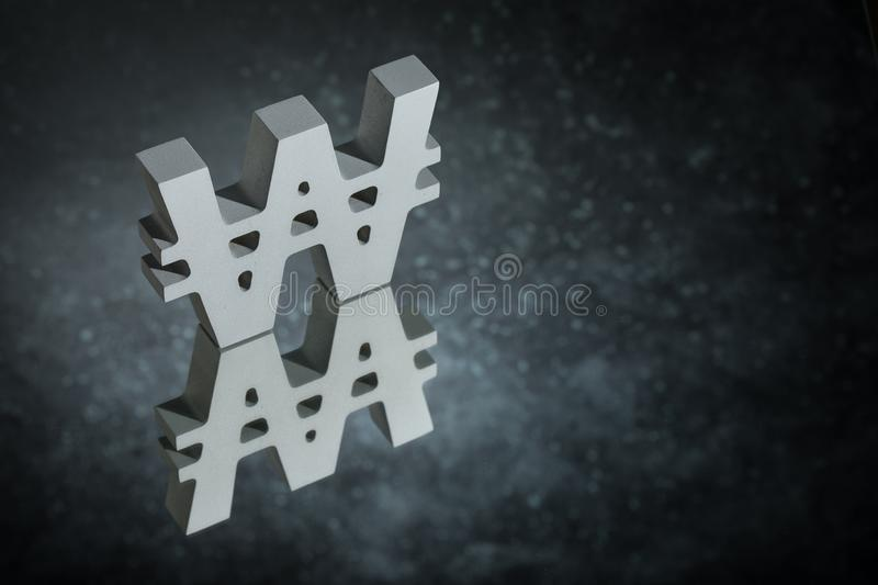 Won Symbol or Sign With Mirror Reflection on Dark Dusty Background. South Korean Currency Symbol or Sign Won With Mirror Reflection on Dark Dusty Background stock photos