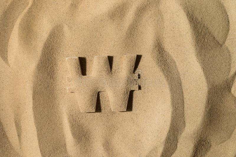 Won Symbol Under the Sand. South Korean Won Symbol or Sign Covered with Sand in the Sun after Crisis stock image