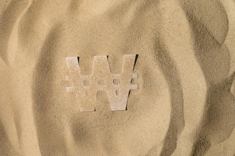 Won Symbol Under the Sand. South Korean Won Symbol or Sign Covered with Sand in the Sun after Crisis royalty free stock photography