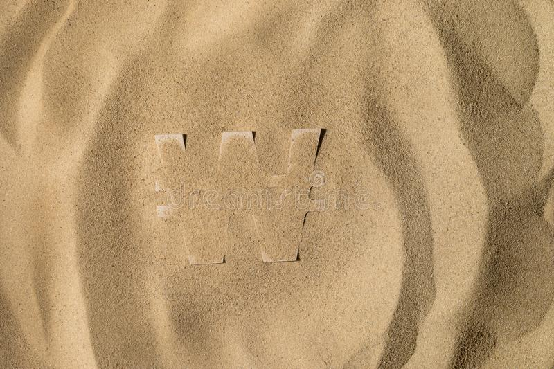 Won Symbol Under the Sand. South Korean Won Symbol or Sign Covered with Sand in the Sun after Crisis royalty free stock photos