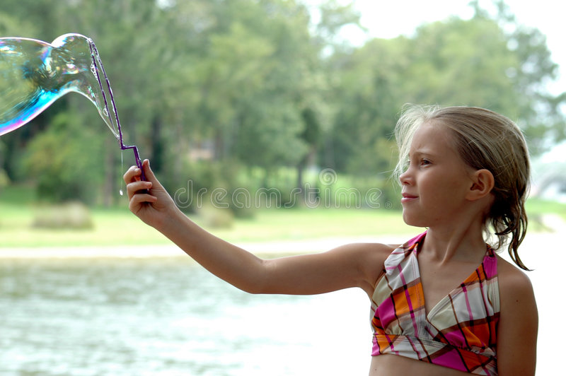 Wonder. Girl plays with bubbles out by the lake stock images
