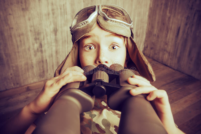 Wonder. Boy plays the pilot, holding binoculars and surprised. Childhood. Fantasy, imagination. Retro style, sepia stock images
