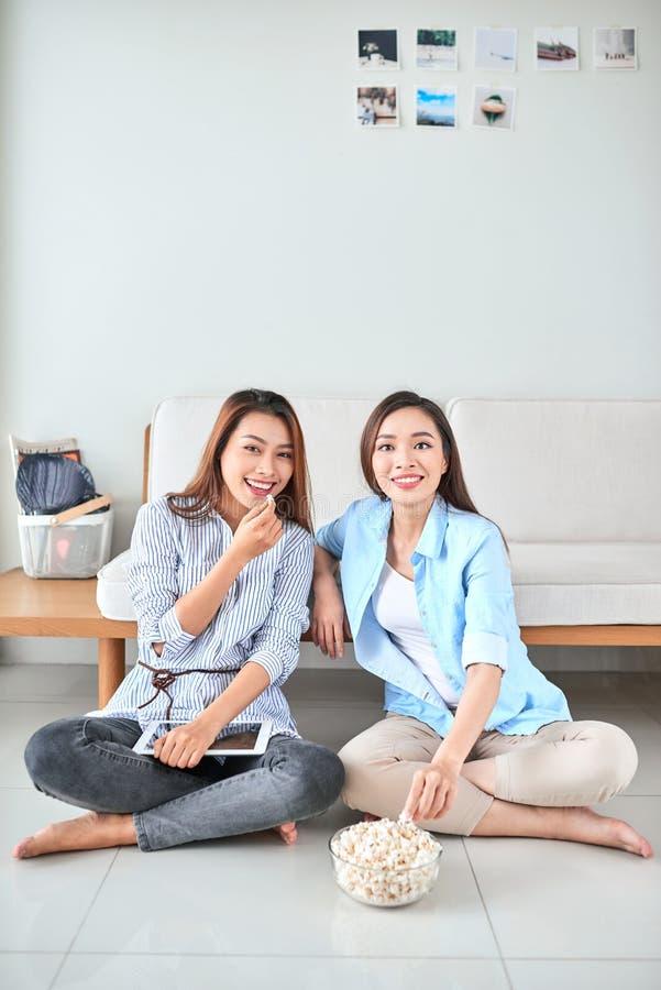 Wondered使打手势食指的被打动的女孩惊奇吃观看与她的朋友的玉米花滑稽的可笑的节目坐在居住 免版税图库摄影
