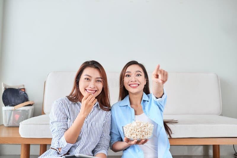 Wondered使打手势食指的被打动的女孩惊奇吃观看与她的朋友的玉米花滑稽的可笑的节目 库存图片