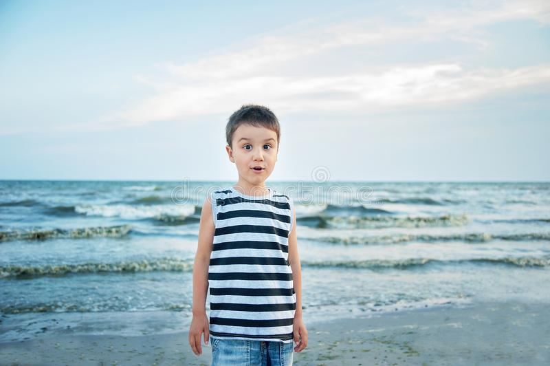 Wondered amazed cute boy in a striped T-shirt at the seaside questioned surprised. Summer vacation. happy kid playing on beach at. The sunset time, adorable stock photo