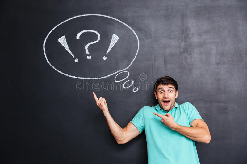 Wondered man pointing on thinking bubble over blackboard background stock photos