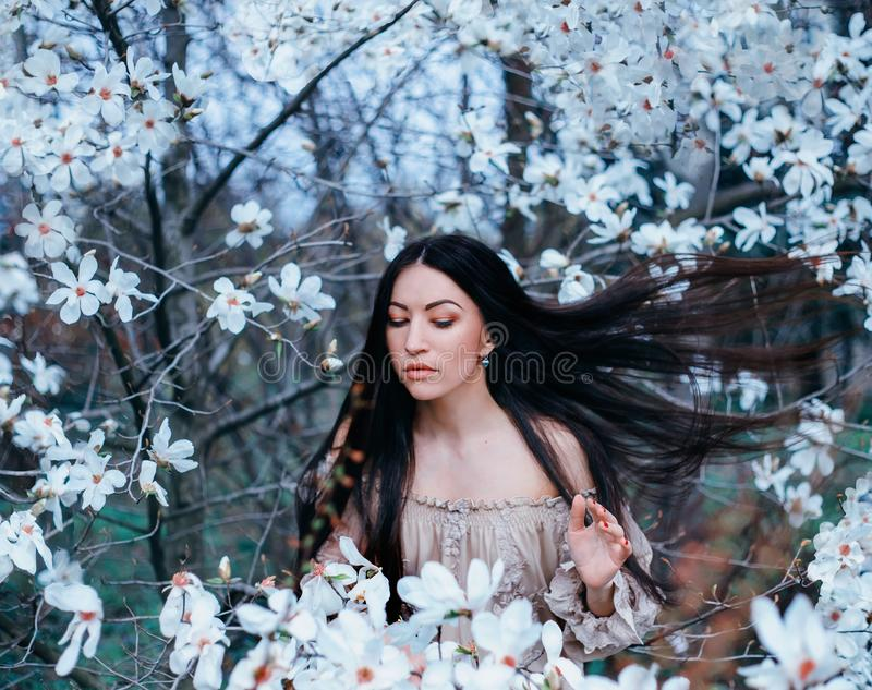 Wonderful attractive dark-haired lady with eyes closed stands in the garden of blooming magnolias. hair flies up with royalty free stock image