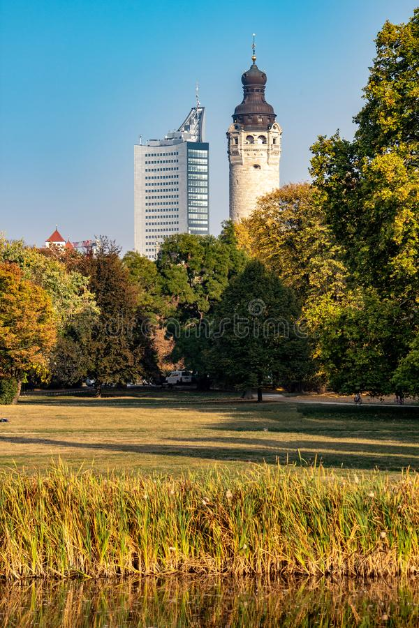 Wonderful autumn panorama with park landscape, city skyscraper, new city hall. And brightly colored trees and leaves in Leipzig royalty free stock image