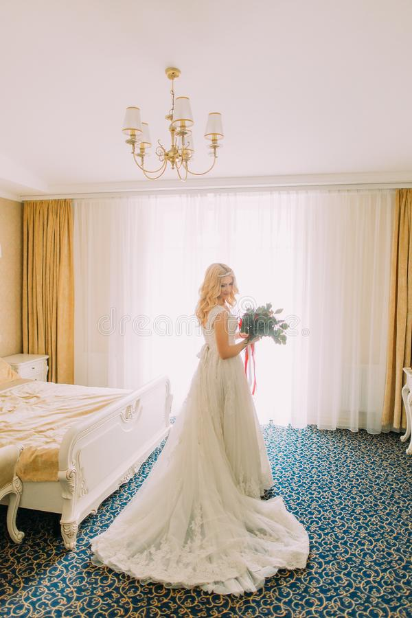 Wonderful blonde bride standing in the bedroom stock images