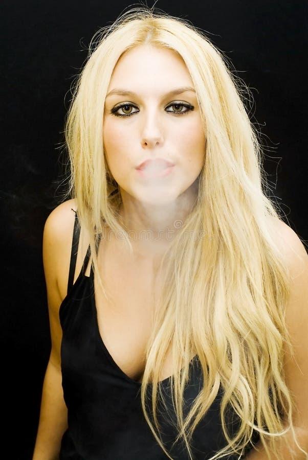 Wonderful blonde smoking. Wonderful blonde woman smoking on black background royalty free stock photography