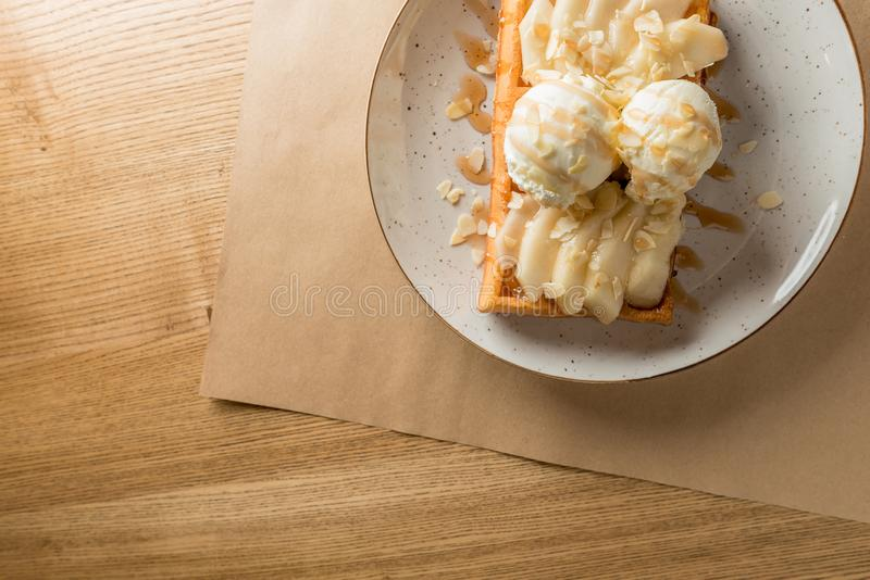 Wonderful breakfast or dessert - vanilla ice cream with caramel sauce on Belgian waffle with slices of ripe pear, top. View royalty free stock photos