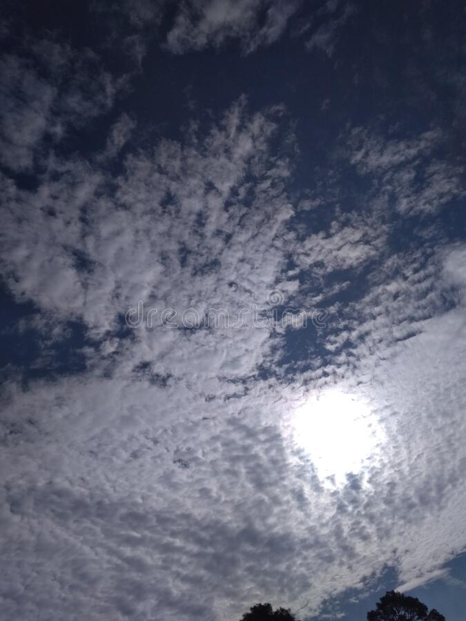 A wonderful close up of an exceptional view of an delightful pattern of white clouds in dark blue sky with shining sun. In the winter over town at Badripur stock photos