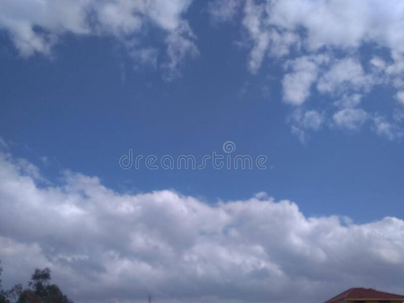 A wonderful close up of a striking view of a lovely pattern of clusters of white clouds. In blue sky with sunlight in the winter at Badripur, Jogiwala, Dehradun stock images