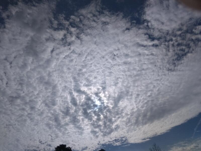 A wonderful close up of a striking view of a pattern of clusters of white clouds. In blue sky with sunlight in the winter stock photo