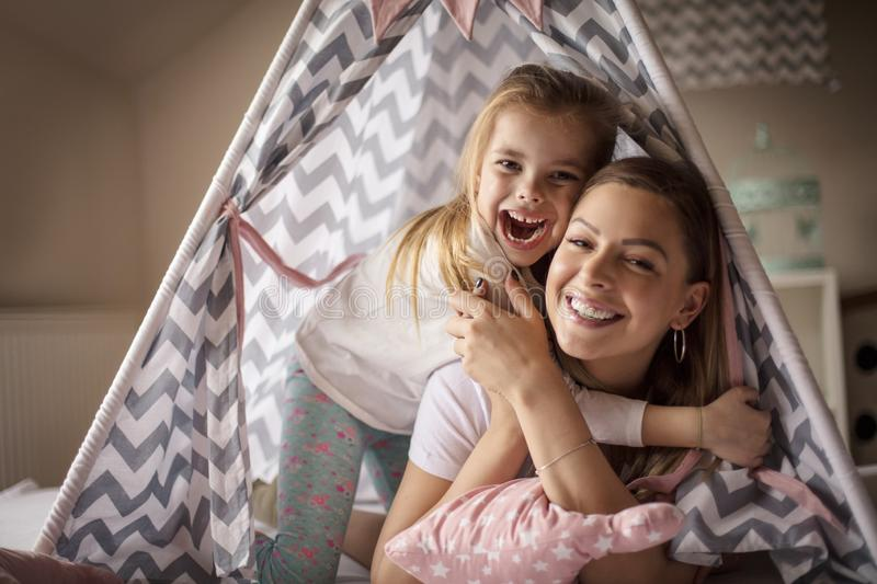 Wonderful fellowship with Mom. Mother and daughter on bed stock image
