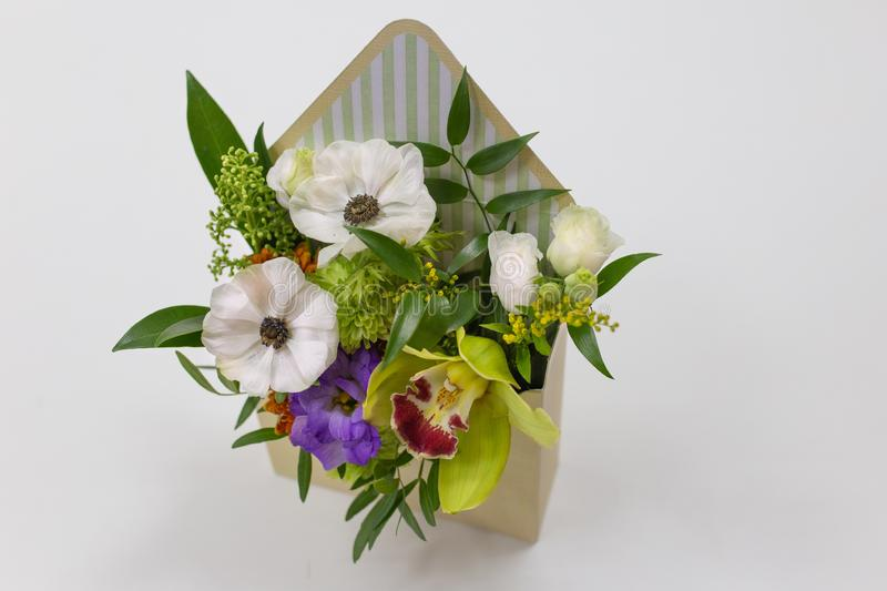 Wonderful floral arrangement of fresh flowers in a box in the form of an envelope on a light background. Flowers: Falinopsis, eustoma, anemone, leaves. Colors royalty free stock image