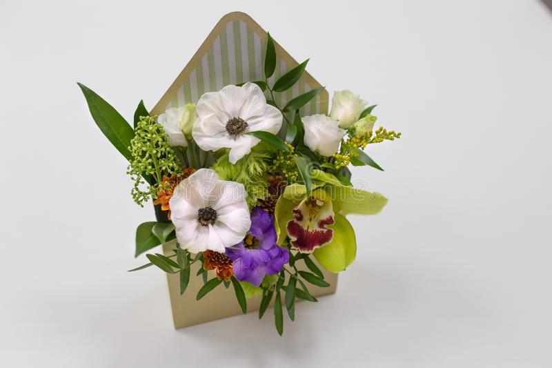 Wonderful floral arrangement of fresh flowers in a box in the form of an envelope on a light background. Flowers: Falinopsis, eustoma, anemone, leaves. Colors royalty free stock photo