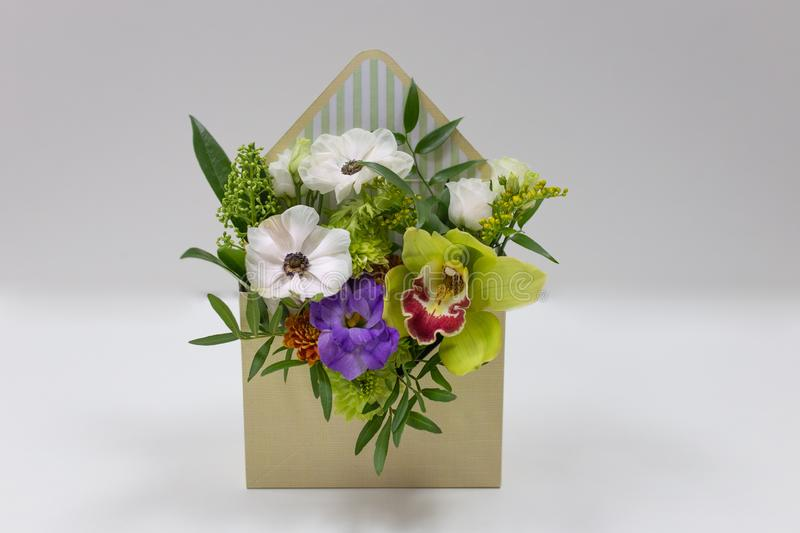 Wonderful floral arrangement of fresh flowers in a box in the form of an envelope on a light background. Flowers: Falinopsis, eustoma, anemone, leaves. Colors royalty free stock photos