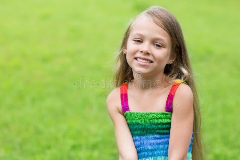 Wonderful girl sitting on the lawn. Wonderful happy girl sitting on the lawn. Girl seven years royalty free stock photos