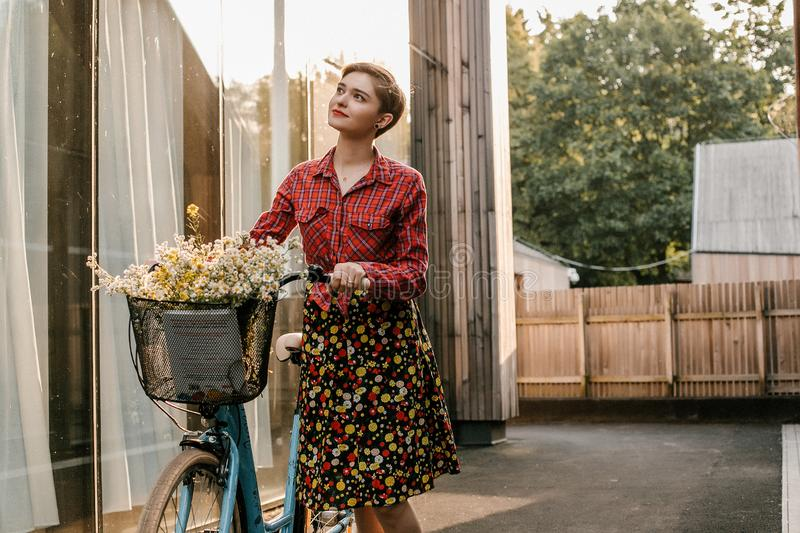 A wonderful girl travels by bike. Walking in the outdoors. Beautiful woman with a basket of flowers. Bike ride royalty free stock images