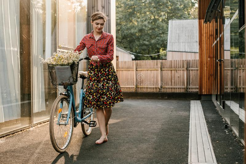 A wonderful girl travels by bike. Walking in the outdoors. Beautiful woman with a basket of flowers. Bike ride royalty free stock image