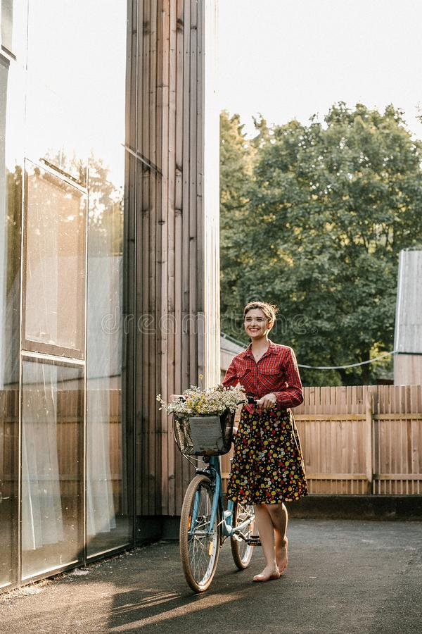 A wonderful girl travels by bike. Walking in the outdoors. Beautiful woman with a basket of flowers. Bike ride royalty free stock photo