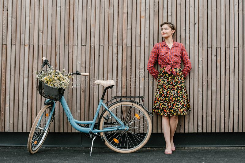 A wonderful girl travels by bike. Walking in the outdoors. Beautiful woman with a basket of flowers. Bike ride stock photos