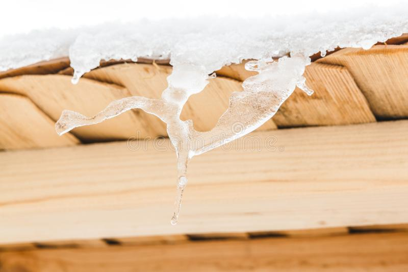 Wonderful icicles melt on the wooden roof with water drops. Spring is comming. Wonderful icicles melt on the wooden roof at the end of winter and water drops stock image