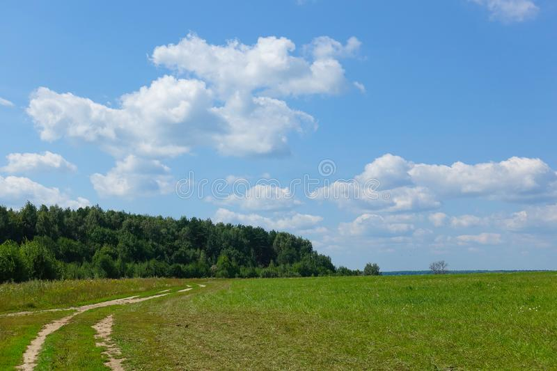 A wonderful landscape for a computer screensaver. Field with dirt road in the field. Sky with clouds royalty free stock image