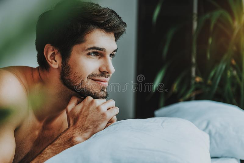 Thoughtful young guy relax in bed in morning stock image