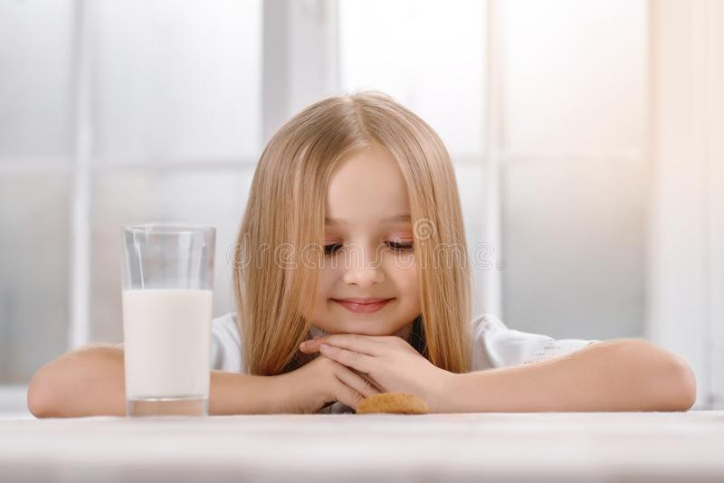 Wonderful little girl with blonde hair sits near milkglass. stock photography
