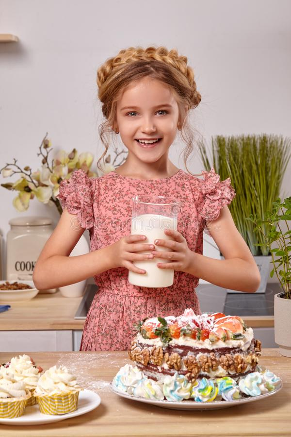 Little girl is making a homemade cake with an easy recipe at kitchen against a white wall with shelves on it. Wonderful little girl wearing in a pink dress is stock photography