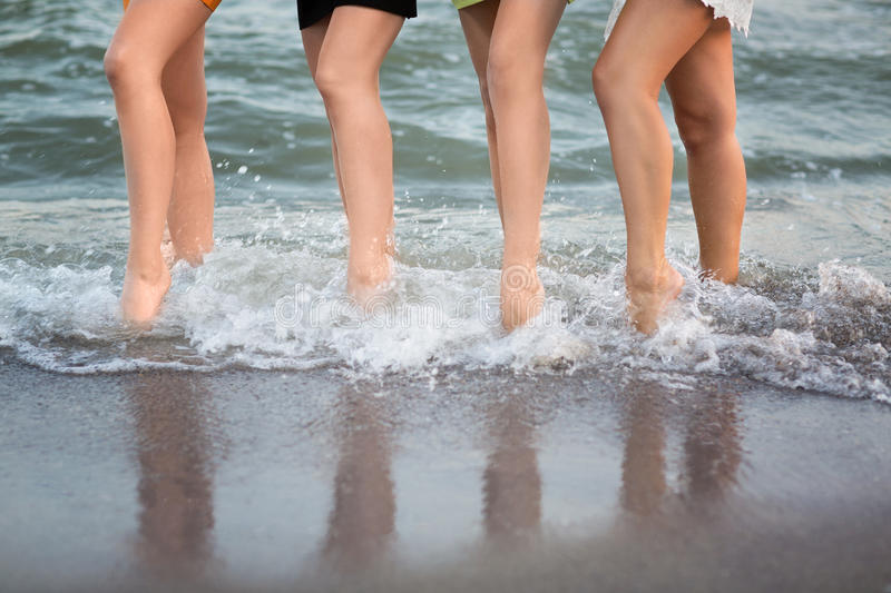 Wonderful long-legged women are walking near the sea on the sand. A cute sports women`s legs. Pretty female legs on the background of the sea. Beautiful stock photography