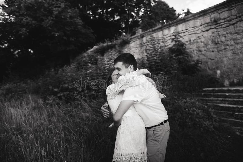 A wonderful love story. Young couple walking around the old wall of castle. Black and white stock photo